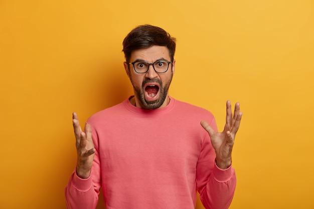 Portret oburzonego mężczyzny stoi w geście wściekłości, głośno krzyczy