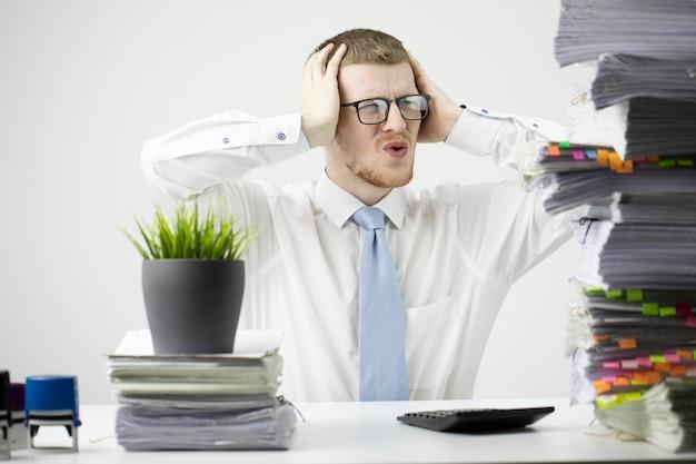 Portret oburzonego, zaskoczony pracownik biurowy w białej koszuli z krawatem