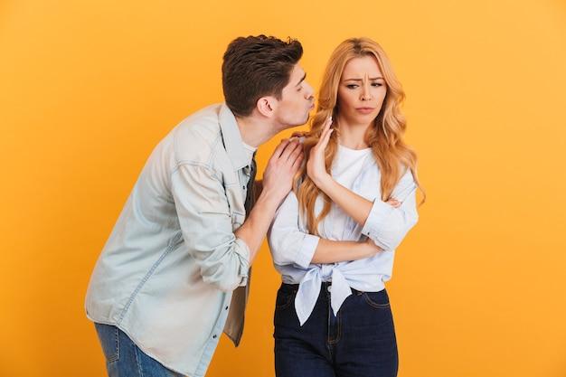 Portret oburzonej niezadowolonej kobiety gestykulującej, by zatrzymać się ręką, podczas gdy mężczyzna próbuje ją pocałować, odizolowany na żółtej ścianie
