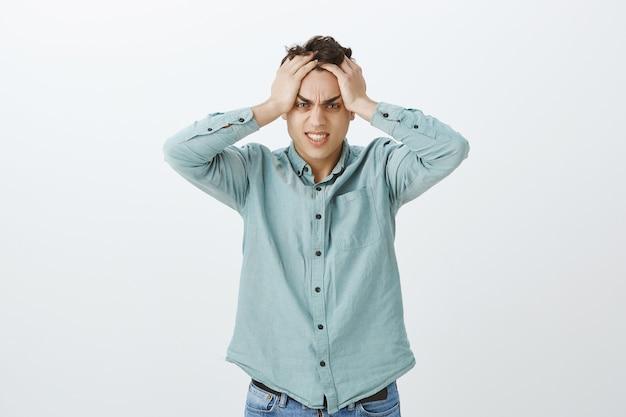 Portret oburzony przygnębiony atrakcyjny facet w zwykłych ubraniach
