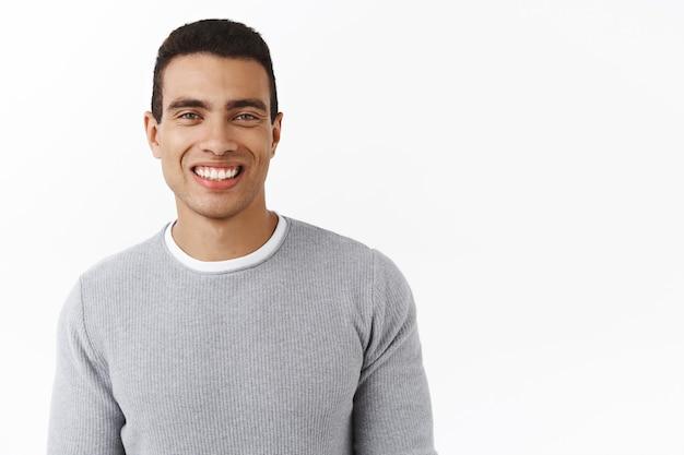 Portret od pasa do góry przyjazny, przystojny, męski mężczyzna z idealnym białym uśmiechem .
