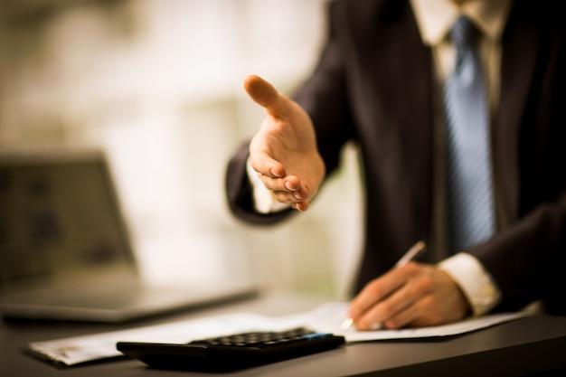 Portret odnoszącego sukcesy biznesmena, który podaje rękę