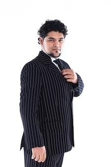 Portret odnoszącego sukcesy biznesmena w garniturze z krawatem na białej ścianie