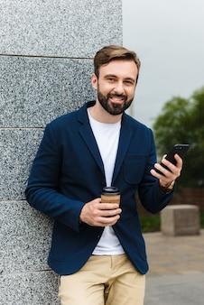 Portret odnoszącego sukcesy biznesmena w kurtce trzymającego telefon komórkowy, stojąc na zewnątrz w pobliżu budynku z kawą na wynos