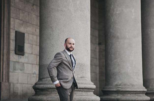 Portret odnoszącego sukcesy brodatego mężczyzny w klasycznym garniturze na tle miasta
