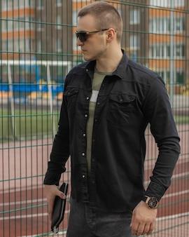 Portret odnoszącego sukcesy dorosłego biznesmena w okularach z czarną koszulą i drogim zegarku
