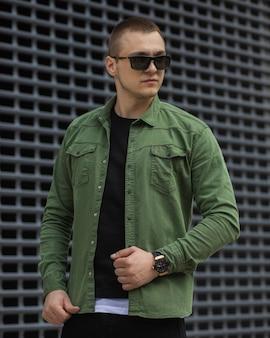 Portret odnoszącego sukcesy dorosłego biznesmena w okularach z zieloną koszulą i drogim zegarku