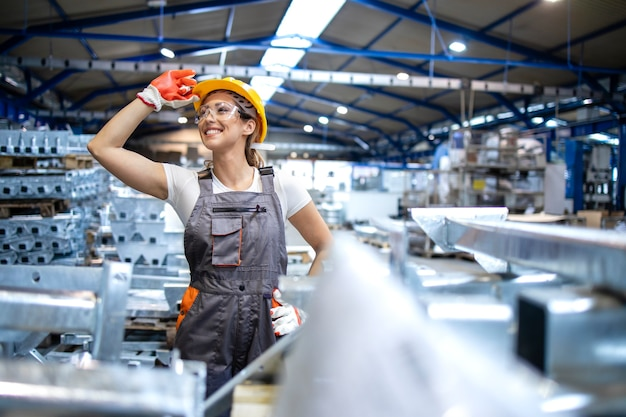 Portret odnoszącego sukcesy pracownika fabryki stojącego w przemysłowej hali produkcyjnej