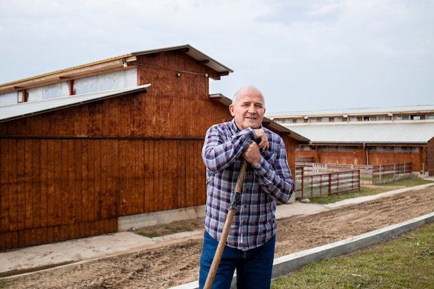 Portret odnoszącego sukcesy rolnika z narzędziem widły i drewnianym domem