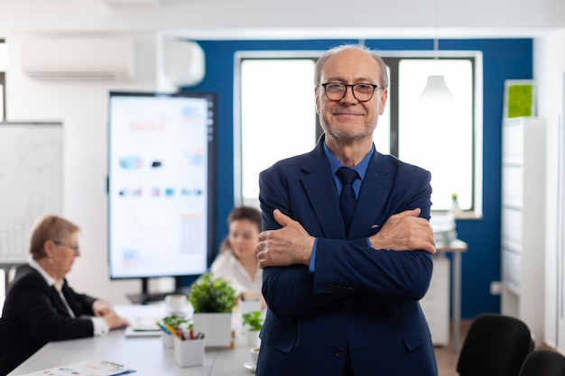 Portret odnoszący sukcesy starszy przedsiębiorca w sali konferencyjnej uśmiechający się do kamery ze skrzyżowanymi rękami