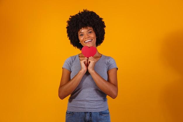 Portret odosobnionej dziewczyny trzymającej papierowe serce na żółto