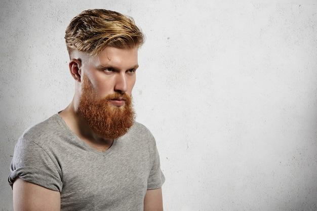 Portret odważnego i modnego modela z długą modną brodą i podciętą fryzurą. kaukaski blondyn w szarym t-shircie ponuro patrzy przed siebie. wewnątrz zdjęcia na białym tle.