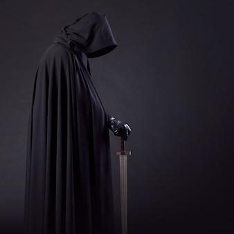 Portret odważnego wędrowca wojownika w czarnym płaszczu i mieczem w dłoni.