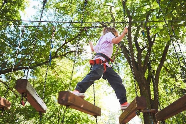 Portret odważnej dziewczynki chodzić po moście linowym w parku linowym przygody. zabawa w parku rozrywki. skaut ćwiczący zjazdy na linie