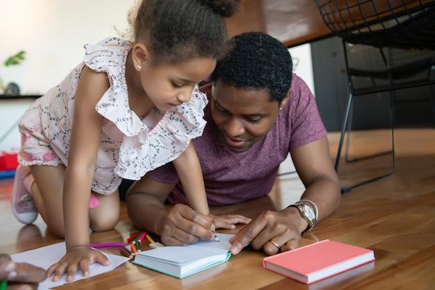 Portret ojca i córki spędzających razem czas i rysując na podłodze podczas pobytu w domu