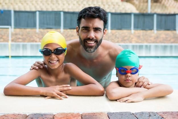 Portret ojca i uśmiechnięte dzieci w basenie