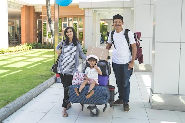 Portret ojca, matki i córki stoi i uśmiecha się spojrzenie na aparat fotograficzny