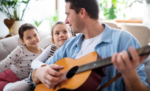 Portret ojca z małymi córkami siedzi na kanapie w domu, grając na gitarze.