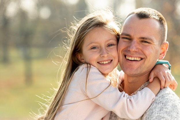 Portret ojciec i córka patrzeje fotografa