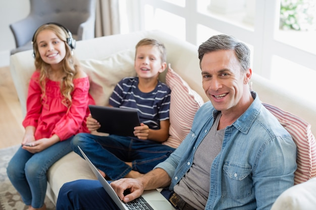 Portret ojciec i dzieciaki używa laptop i cyfrową pastylkę w żywym pokoju