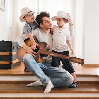 Portret ojciec z jego dwa synami trzyma gitarę
