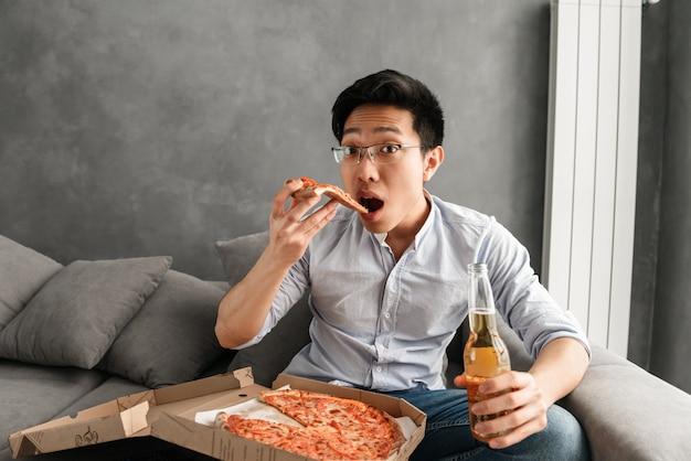 Portret okaleczający młody azjatykci mężczyzna łasowania pizza