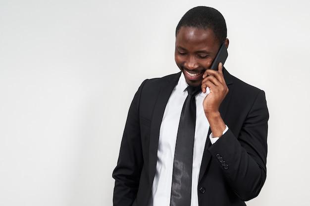 Portret ono uśmiecha się afrykański mężczyzna podczas gdy opowiadający na telefonie z szarości ścianą