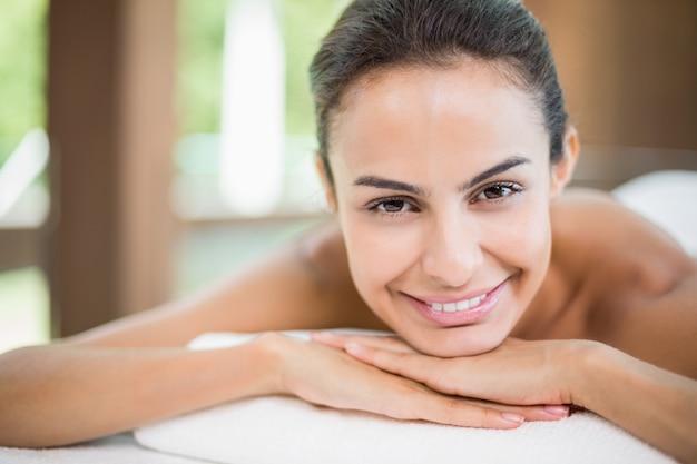 Portret ono uśmiecha się młoda kobieta podczas gdy odpoczywający na masażu stole