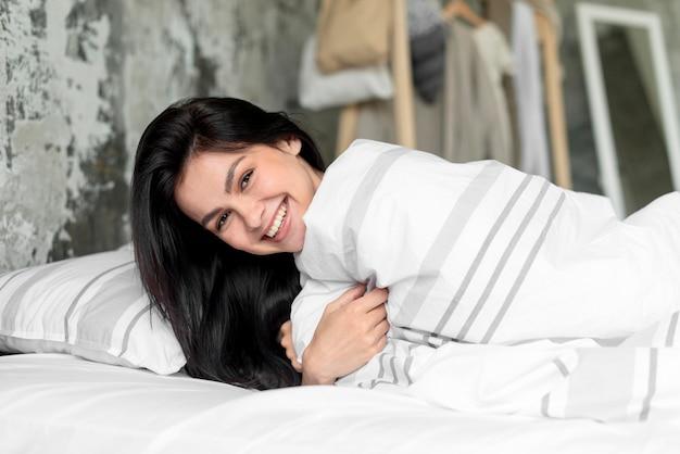 Portret ono uśmiecha się w łóżku młoda kobieta