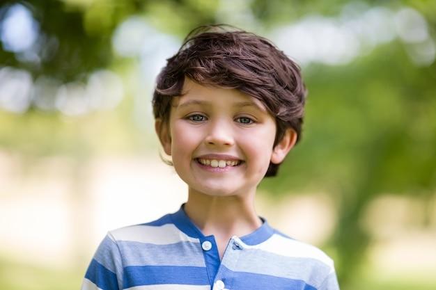 Portret ono uśmiecha się w parku chłopiec
