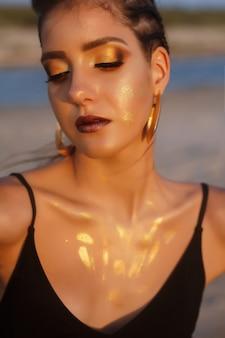 Portret opalonego modelu ze złotym makijażem oraz w stroju kąpielowym na morzu. artystyczne rozmycie tła. koncepcja