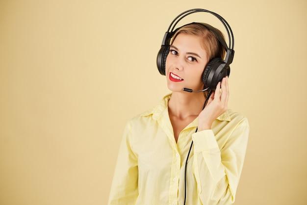 Portret operatora pomocy technicznej w zestawie słuchawkowym, który ma problemy z połączeniem, odizolowany na jasnożółtym tle