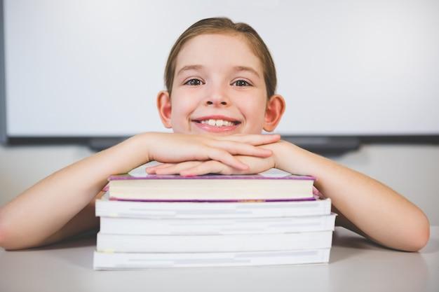 Portret opiera na stercie książki w klasowym pokoju uśmiechnięta dziewczyna