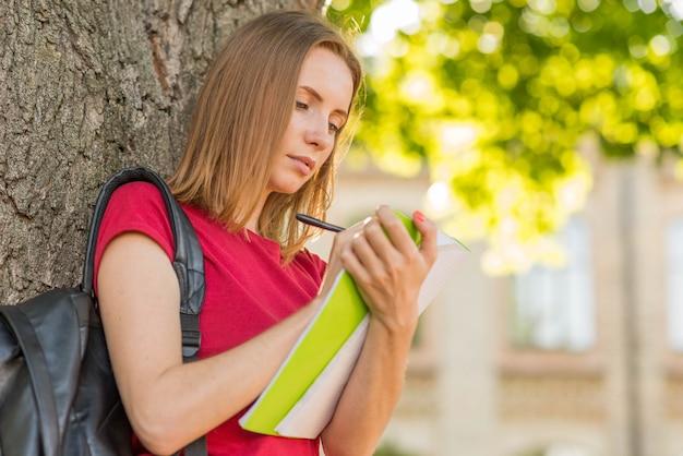 Portret opiera przeciw drzewu uczennica