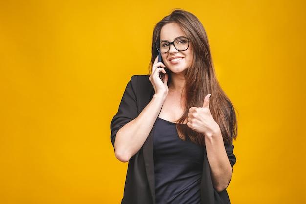 Portret opowiada na telefonie komórkowym pokazuje kciuka up znaka młoda kobieta nad kolor żółty ścianą.