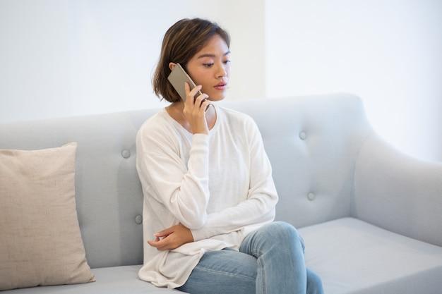 Portret opowiada na telefonie komórkowym w domu ufna młoda kobieta