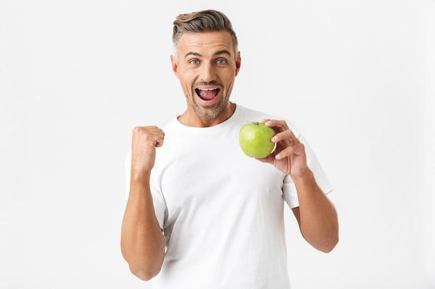 Portret optymistycznego mężczyzny w wieku 30 lat, który ma włosie w casualowej koszulce, pozuje i trzyma w ręku zielone jabłko na białym tle