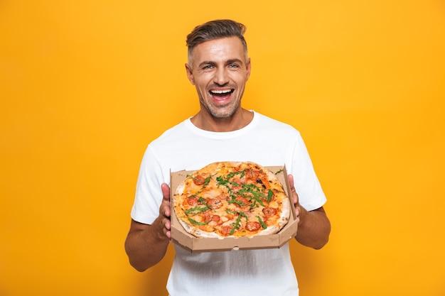 Portret optymistycznego mężczyzny w wieku 30 lat w białej koszulce, trzymającego i jedzącego pizzę, stojącego odizolowanego na żółto