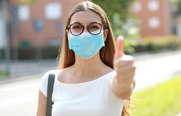 Portret optymistycznej dziewczyny noszącej maskę ochronną pokazując kciuk na ulicy miasta