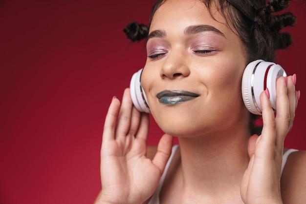Portret optymistycznej dziewczyny punkowej z dziwaczną fryzurą i zamkniętymi oczami, uśmiechającej się podczas słuchania muzyki przez słuchawki izolowane nad czerwoną ścianą