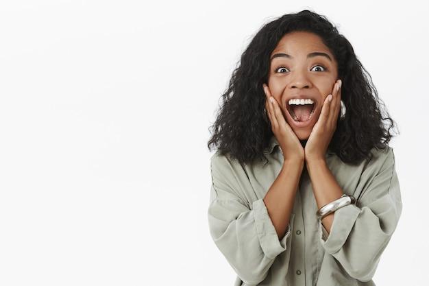Portret optymistycznej, entuzjastycznej i zachwyconej dziewczyny o ciemnej karnacji z kręconymi włosami, krzyczącej ze zdumienia i radości