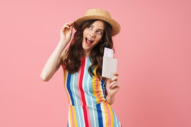 Portret optymistycznej marzącej szczęśliwej młodej uroczej kobiety pozującej na białym tle nad różową ścianą trzymającą paszport z biletami