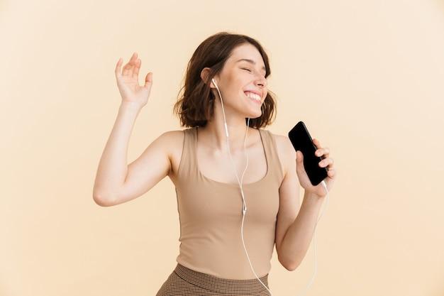 Portret optymistycznej młodej kobiety ubranej w zwykłe ubrania śpiewającej podczas słuchania muzyki przez słuchawki i telefon komórkowy na białym tle