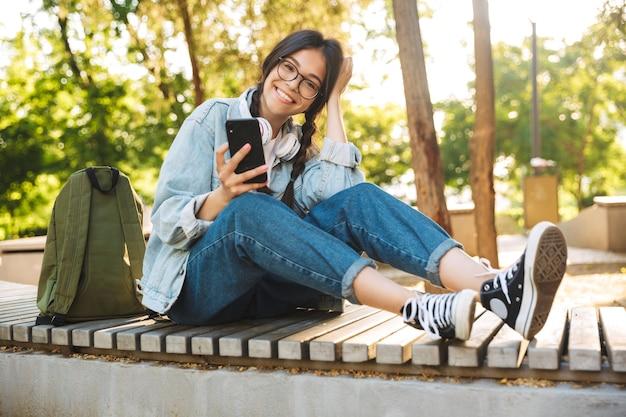 Portret optymistycznej pozytywnej ślicznej młodej studentki w okularach, siedząc na ławce na świeżym powietrzu w parku przyrody przy użyciu telefonu komórkowego na czacie.
