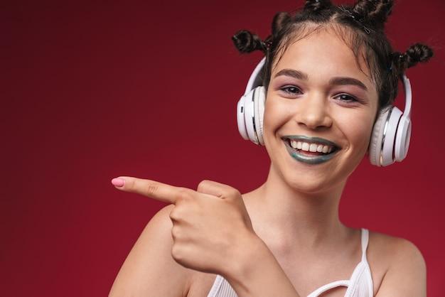 Portret optymistycznej punkowej dziewczyny z dziwaczną fryzurą wskazującą palcem na copyspace podczas słuchania muzyki przez słuchawki izolowane nad czerwoną ścianą
