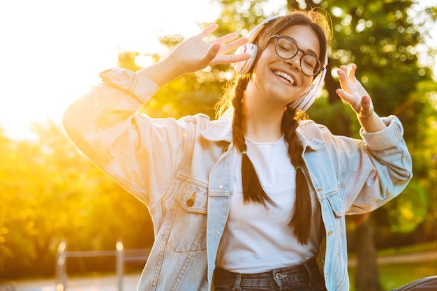 Portret optymistycznej wesołej młodej nastoletniej dziewczyny siedzącej na zewnątrz w pięknym zielonym parku słuchającej muzyki przez słuchawki