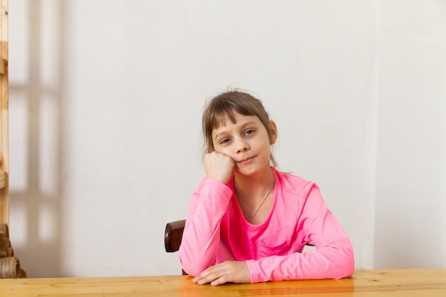 Portret ośmioletniej dziewczyny na krześle, myśląc