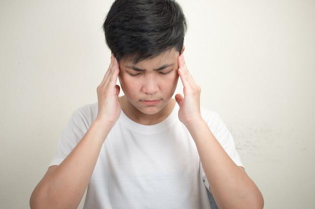 Portret osoby azjatyckiej na sobie białą koszulę z bólem głowy.