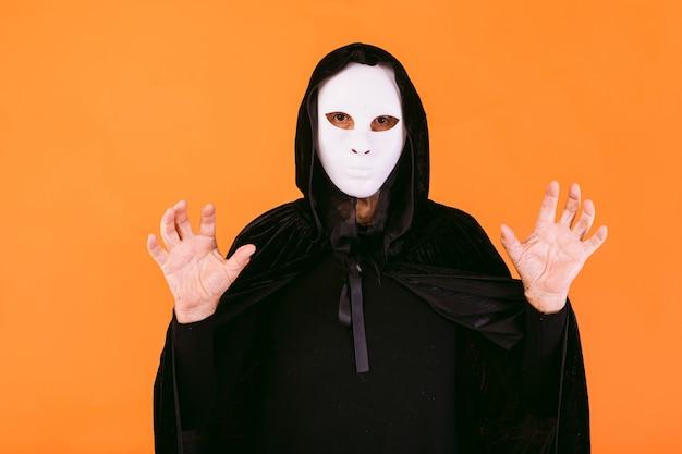 Portret osoby w białej masce zabójcy halloween, pelerynie i kapturze, patrzącej w kamerę, straszącej rękami, ubranej na halloween na pomarańczowym tle