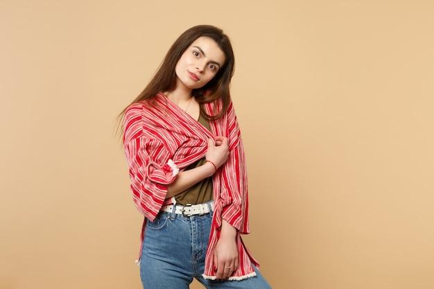 Portret oszałamiająca atrakcyjna młoda kobieta w stroju casual stojący, patrząc na kamerę na białym tle na pastelowym beżowym tle w studio. ludzie szczere emocje, koncepcja stylu życia. makieta miejsca na kopię.